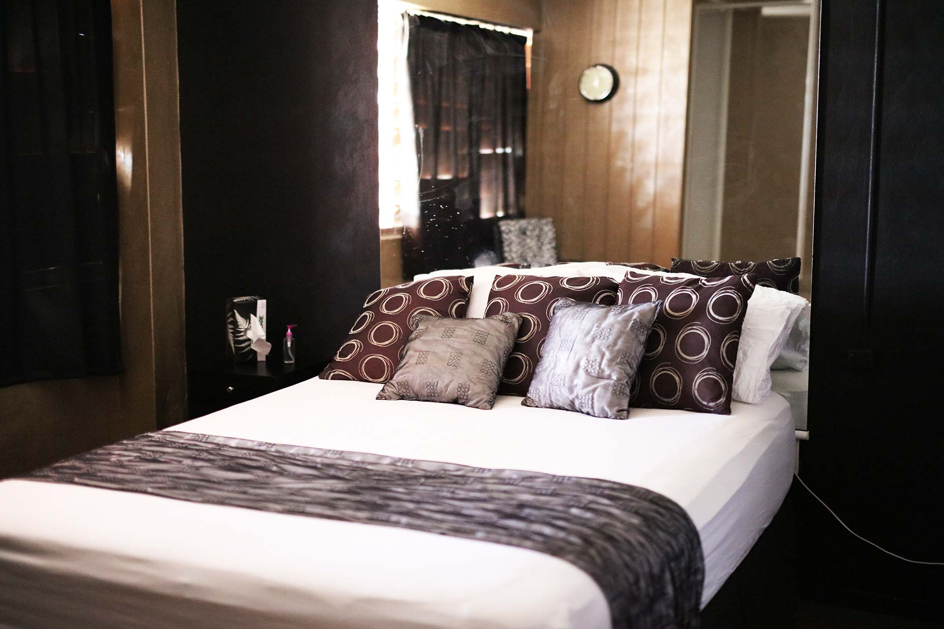 white bed with brown and silver cushions