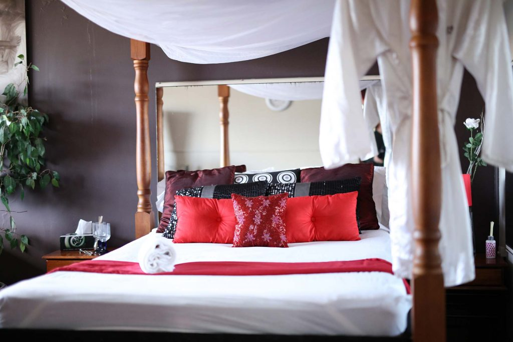 four poster bed with black and red cushions