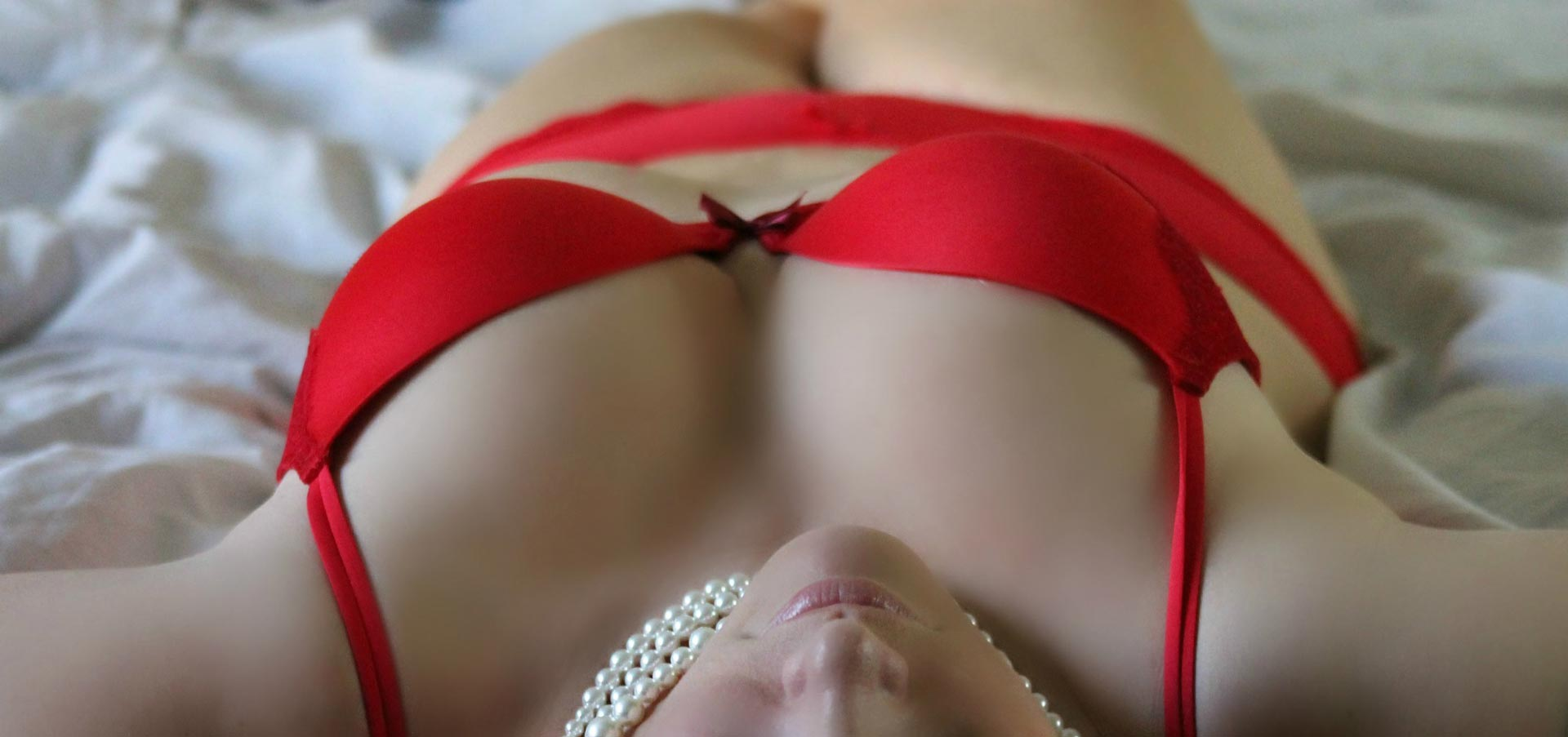 woman with pearl necklace wearing red lingere lying back on white sheets